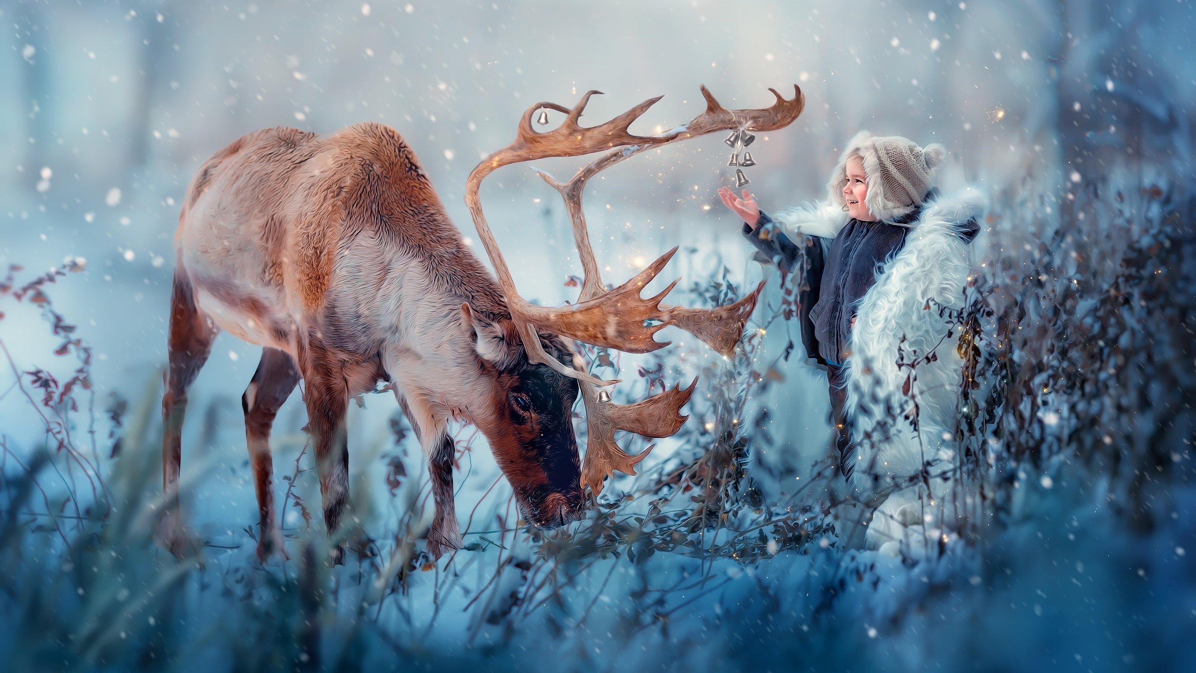 Fondos de pantalla Reno con un niño en la nieve