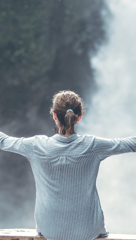 Fondos de pantalla Chica en columpio cerca de una cascada Vertical