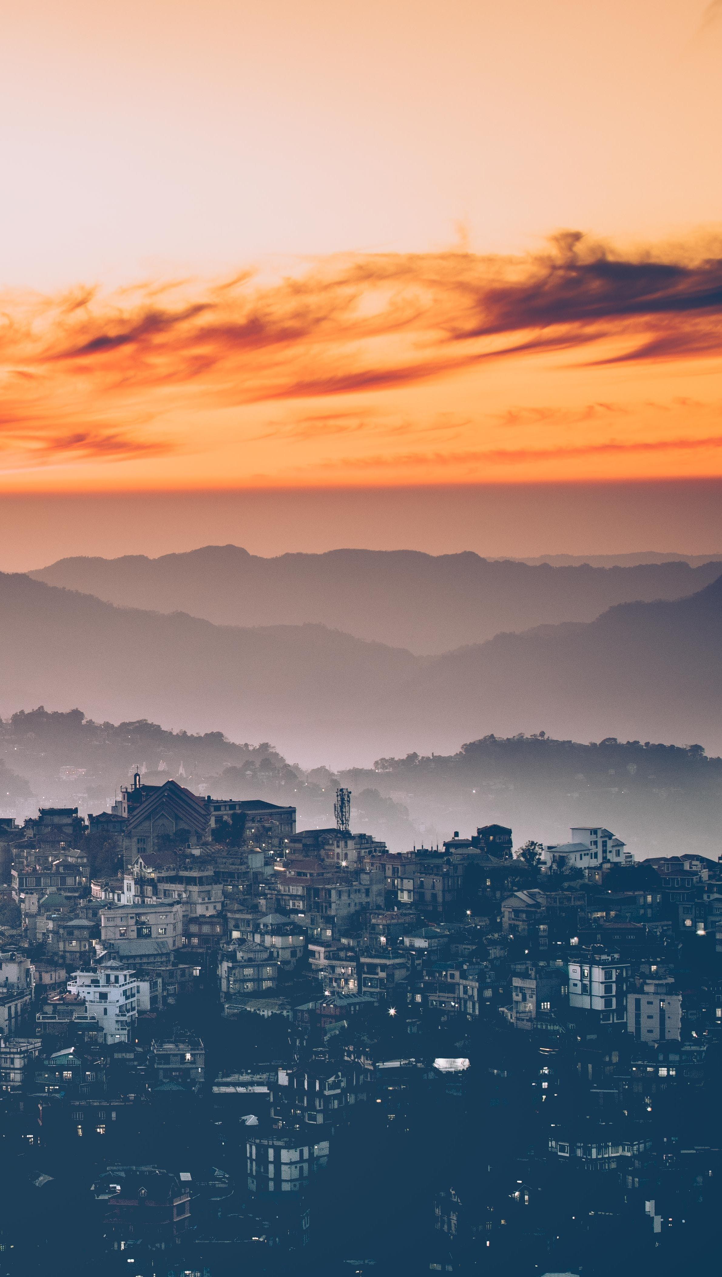 Fondos de pantalla Ciudad y montañas con Puesta de sol Vertical