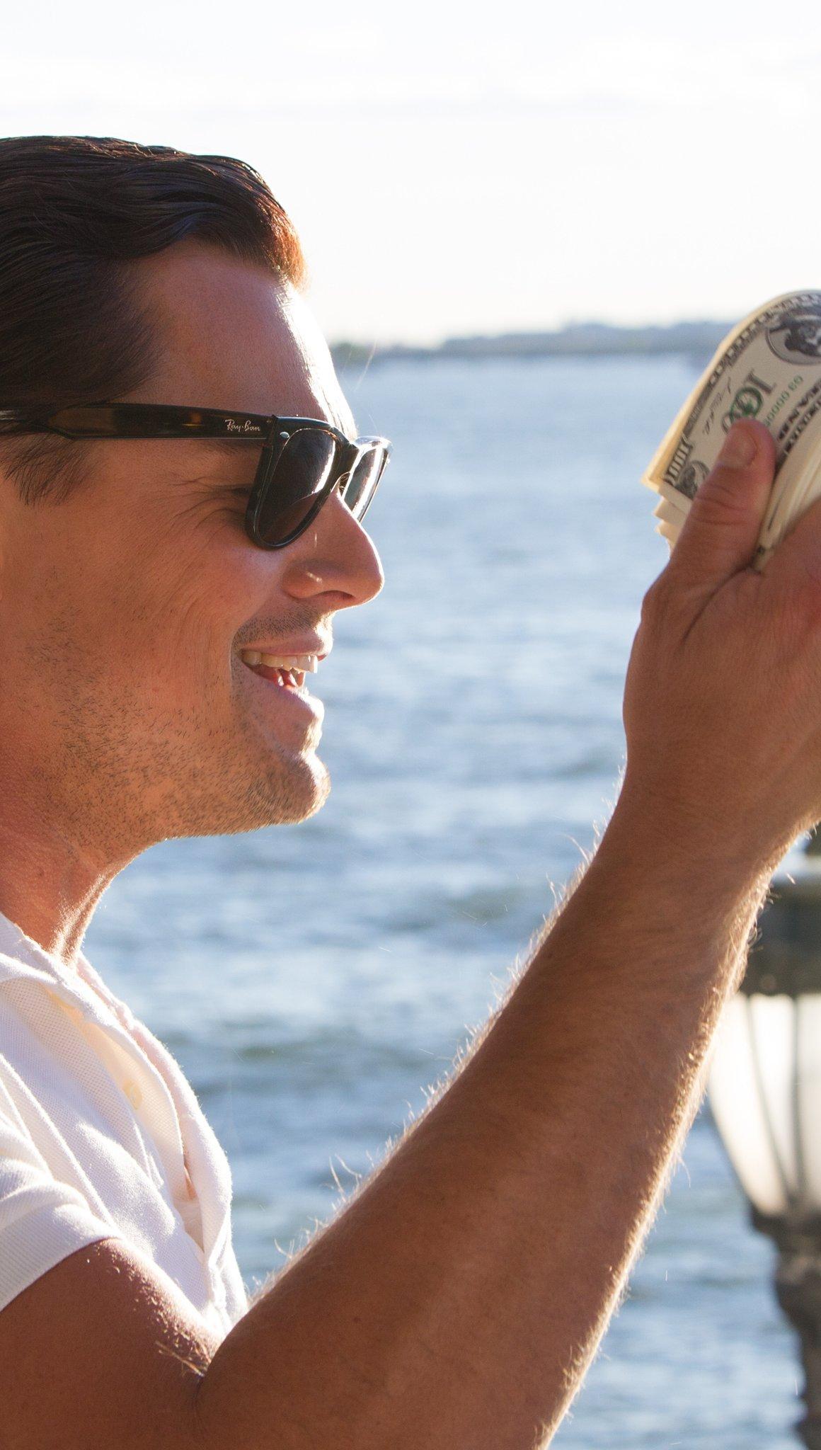 Fondos de pantalla El lobo de Wall Street con dinero en la mano Vertical