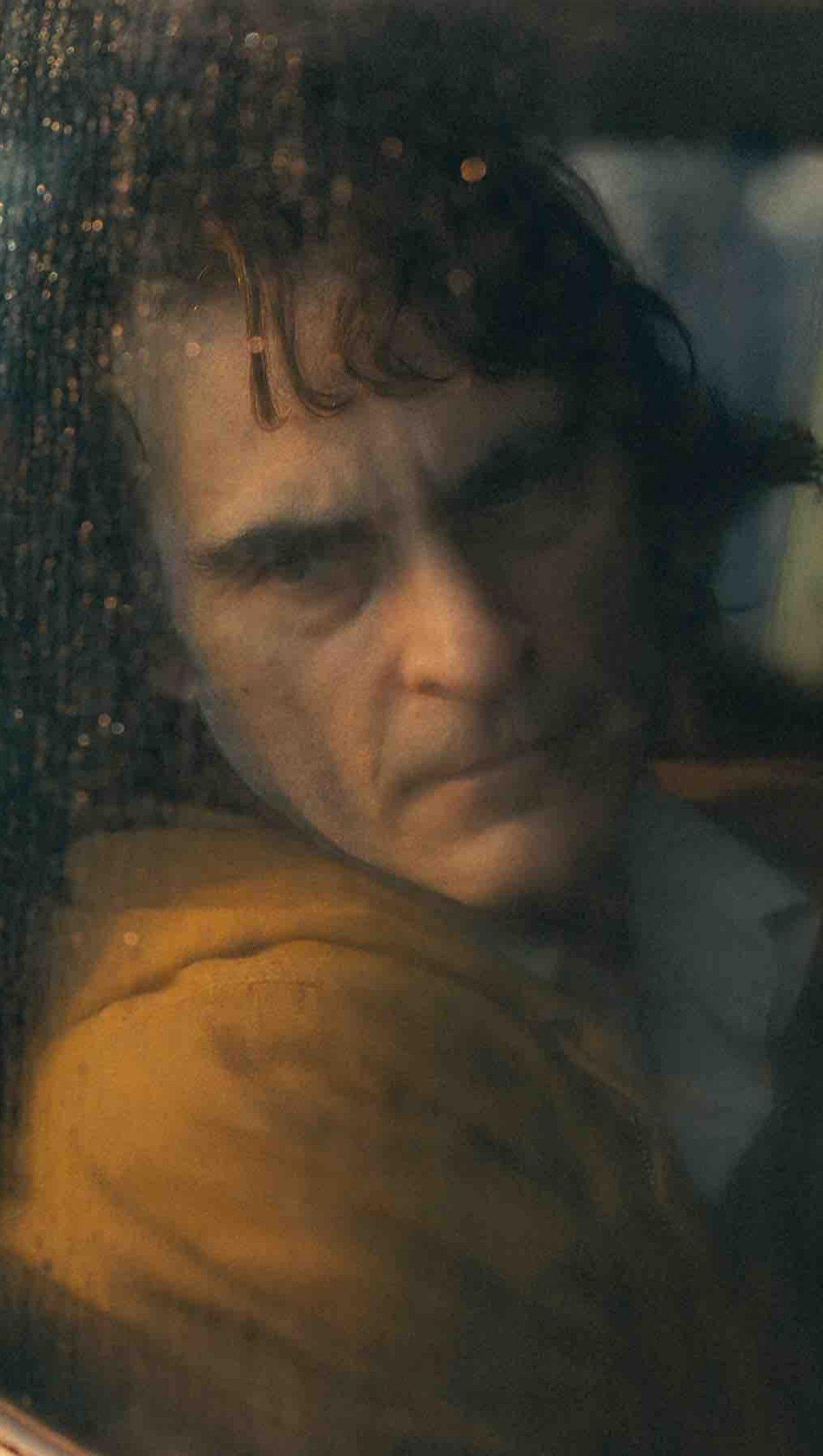 Wallpaper Joaquin Phoenix in train in Joker Vertical